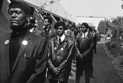 Black Panthers members standing in two long rows with their hands folded in front of them.